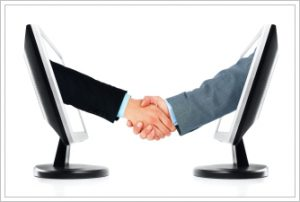 A business handshake between two computer monitors. Isolated on a white background.